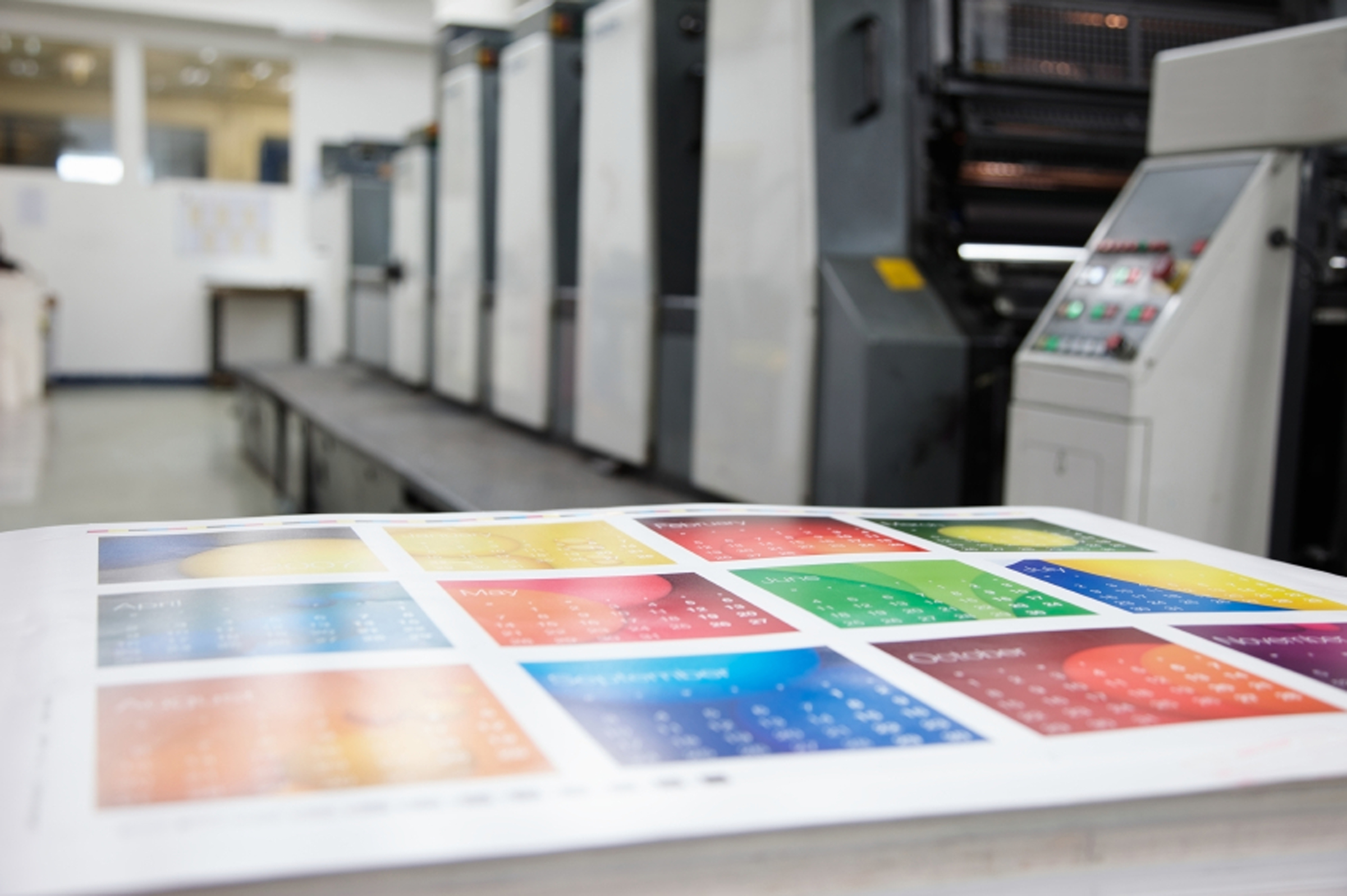 A colourful printed calendar sheet in a press room.